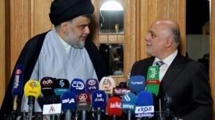 رئيس الوزراء العراقي حيدر العبادي (يمين) يشارك في مؤتمر صحافي مع الزعيم الشيعي البارز مقتدى الصدر في 23 حزيران/يونيو في النجف