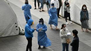 Du personnel médical guide les visiteurs d'un centre de tests du Covid-19 à Séoul, le 12 mai 2020