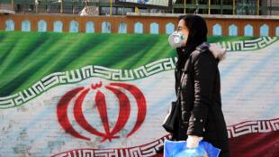امرأة إيرانية تضع كمامة تسير قرب جدارية لعلم بلادها في طهران في 4 آذار/مارس 2020