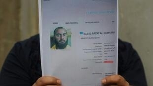 رجل عراقي يحمل صورة عن ملف أبو بكر البغدادي المطلوب لدى السلطات العراقية وقد نشرت في 6 شباط/فبراير.
