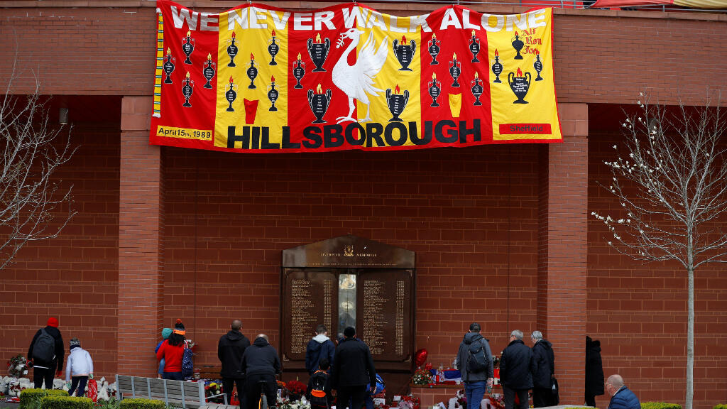 """Una bandera con la leyenda """"Nunca caminamos solos"""" acompaña el monumento en el exterior del estadio de Anfield, del Liverpool F.C., en honor a las víctimas de la tragedia de Hillsborough en la que perdieron la vida 96 personas el 15 de abril de 1989."""