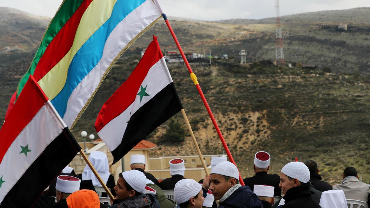 Miembros de la minoría religiosa drusa protestan en Majdal Shams con banderas drusas y sirias durante el aniversario de la anexión israelí de los Altos del Golán a su territorio el 14 de febrero de 2019.