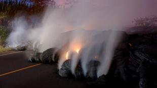 Gases volcánicos emanan desde una de las fisuras del volcán Kilauea en Hawái. La lava ha obstruído diversas carreteras en la zona. Mayo 28 de 2018.