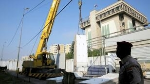 Workers remove cement blast walls surrounding the Iraqi foreign ministry near Baghdad's Green Zone on December 23, 2018