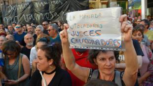 Una mujer sostiene una pancarta el 21 de junio de 2018 en Pamplona después de que un tribunal ordenara la libertad bajo fianza de cinco hombres sentenciados a nueve años de prisión por abusar sexualmente de una joven en el festival de toros de Pamplona.
