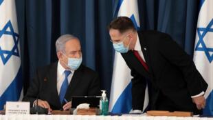 رئيس الوزراء الإسرائيلي بنيامين نتانياهو (يسار) يضع كمامة واقية ويستمع إلى سكرتير الاجتماع الحكومي الأسبوعي تساخي برافيرمان في مستهل الاجتماع الأسبوعي في وزارة الخارجية الإسرائيلية في القدس في الخامس من تموز/يوليو 2020