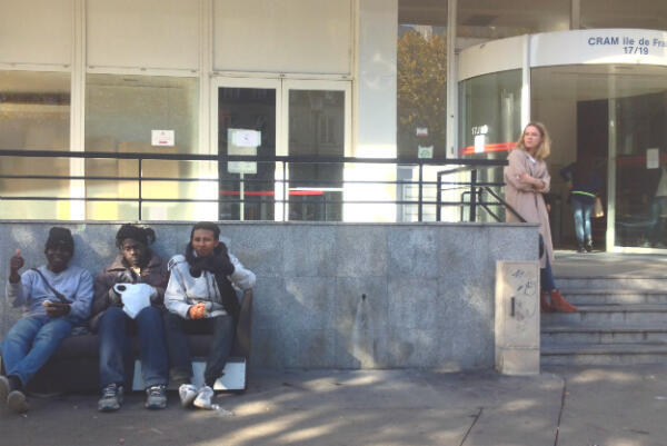 Youssif, Mohammad, and Osmane sit in front of the state health insurance office on Avenue Flandre