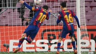 نجم برشلونة الارجنتيني ليونيل ميسي (يسار) لحظة تسجيله برأسه الهدف رقم 643 في صفوف برشلونة ليعادل الرقم القياسي للاسطورة البرازيلي بيليه في صفوف ناد واحد. 19 كانون الاول/ديسمبر 2020