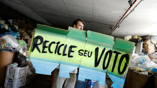 """El artista y activista brasileño Mundano sostiene un cartel que dice """"Recicla tu voto"""", cuando Fernando Haddad, candidato presidencial del Partido de los Trabajadores (PT) de Brasil, llega a la cooperativa Coopemare, que emplea a personas para ayudar a clasificar la basura recolectada en las residencias, mercados y tiendas, que luego se venden a empresas de reciclaje, en el barrio Pinheiros de Sao Paulo, Brasil, el 22 de octubre de 2018."""