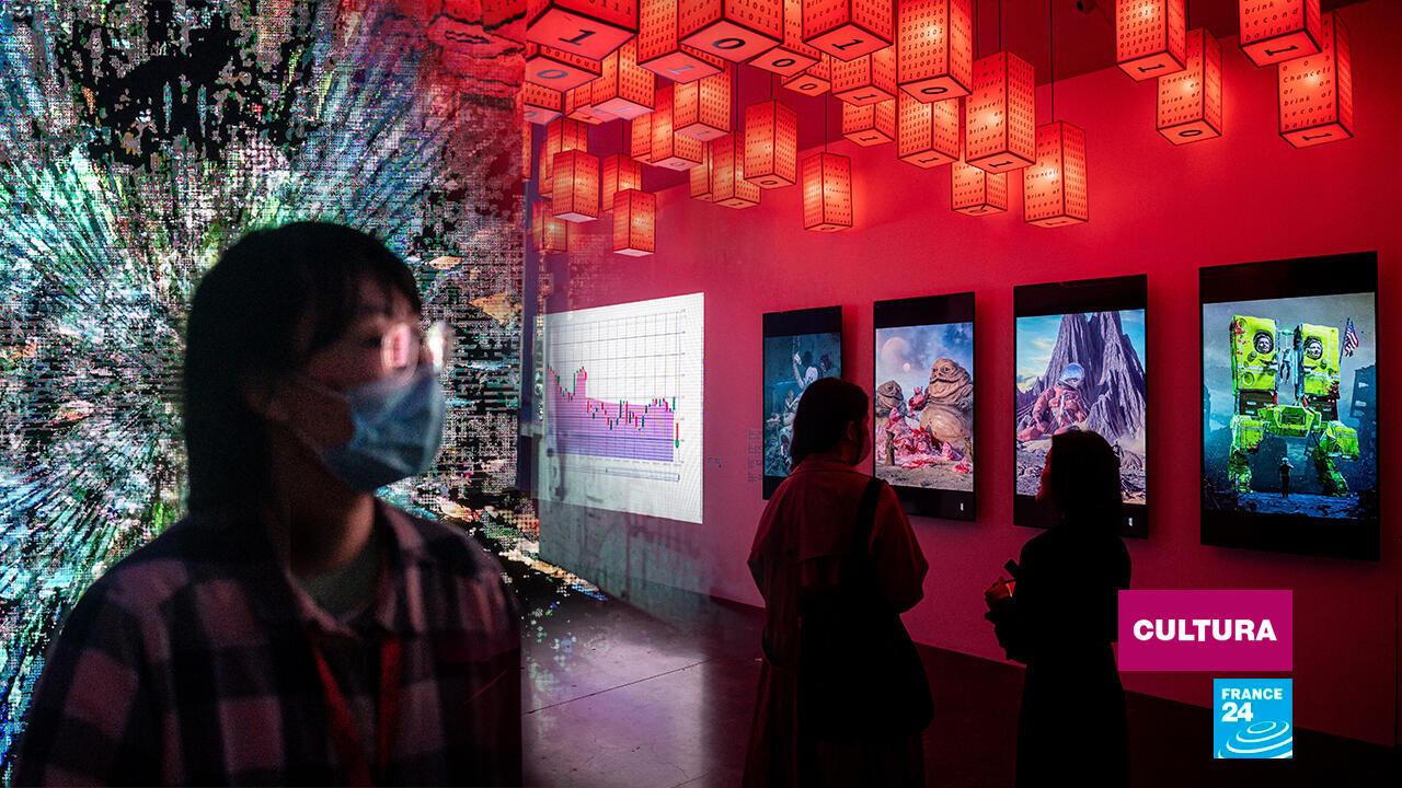 Una mujer camina frente a la pintura digital del artista chino Liu Gang, mientras que otras dos visitantes aprecian las obras del estadounidense mundialmente famoso 'Beeple'.