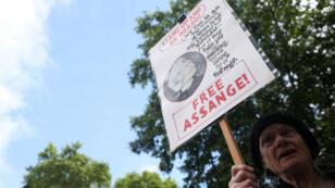 Una manifestante sostiene un cartel de protesta frente al Tribunal de Magistrados de Westminster, donde se celebró la audiencia preliminar de Julian Assange, en Londres, Gran Bretaña, el 14 de junio de 2019.