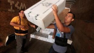 Trabajadores cargan material electoral antes de su distribución en Tegucigalpa, el 20 de noviembre de 2017.