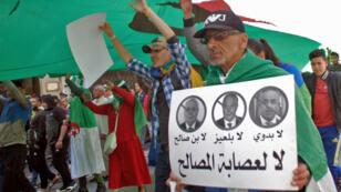 """Un manifestant algérien brandit une pancarte contre les """"3B"""" (Abdelkader Bensalah, Tayeb Belaiz et Noureddine Bedoui) lors du premier vendredi de manifestations, le 12 avril 2019."""