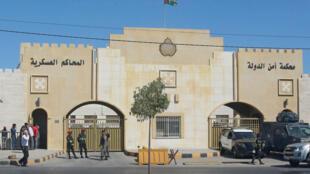 شرطيون خارج محكمة أمن الدولة حيث جرت الاثنين محاكمة مسؤولَين متهمين بمساعدة الأمير الأردني حمزة في محاولة الإطاحة بأخيه غير الشقيق الملك عبد الله الثاني، في عمان في 21 حزيران/يونيو 2021
