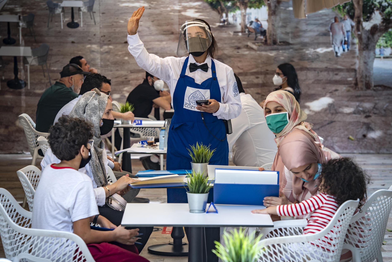 أشخاص يرتدون كمامات، يجلسون في مقهى بالرباط.
