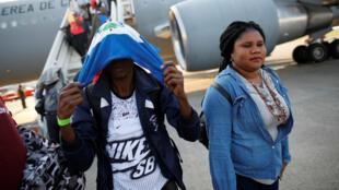 Un hombre haitiano se cubre la cara con una bandera luego de desembarcar de un avión de la Fuerza Aérea de Chile al llegar al Aeropuerto Internacional de Puerto Príncipe, Haití, el 7 de noviembre de 2018.