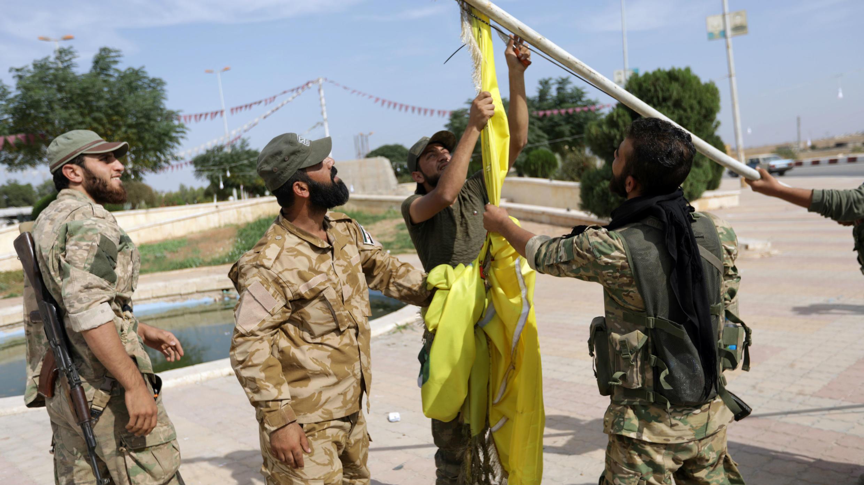 Los combatientes rebeldes sirios respaldados por Turquía derriban la bandera del Consejo Militar de Tal Abyad en la ciudad fronteriza de Tal Abyad, Siria, el 14 de octubre de 2019.