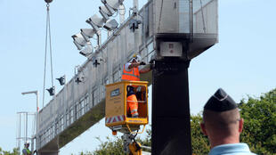 Un gendarme surveillant le démontage d'un portique chargé de contrôler l'écotaxe, le 23 juin 2014.