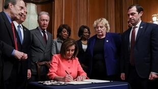 US House Speaker Nancy Pelosi surrounded by the House impeachment managers and committee chairs as she signs the two articles of impeachment of US President Donald Trump, Washington, USA, January 15, 2020.