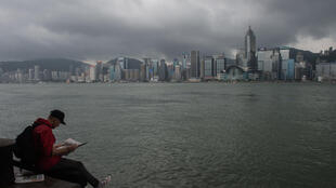 A man reads a newspaper on the edge of a promenade overlooking Victoria Harbour in Hong Kong