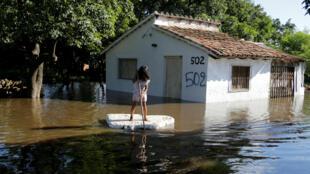 Una niña usa un trozo de espuma de poliestireno como remo junto a una casa inundada después de que las fuertes lluvias causaron el desbordamiento del río Paraguay, en las afueras de Asunción, Paraguay el 23 de enero de 2018.
