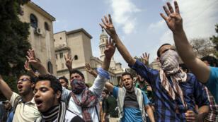 """Estudiantes egipcios, partidarios de la Hermandad Musulmana y el derrocado presidente islámico Mohamed Morsi, muestran el símbolo de cuatro dedos conocido como """"Rabaa"""", que significa cuatro en árabe, que está asociado con los asesinados en la campaña contra el campamento de protesta Rabaa al-Adawiya en El Cairo, mientras se manifestaban fuera de la Universidad de El Cairo, el 9 de abril de 2014."""