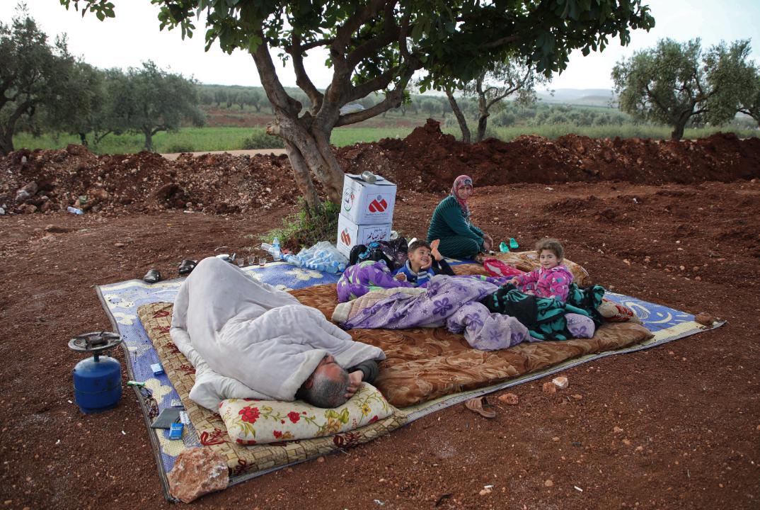Un grupo de sirios mientras aguardaba en una zona cercana a un campamento para desplazados en la aldea de Atme, en la provincia de Idlib del norte, el 8 de mayo de 2019.