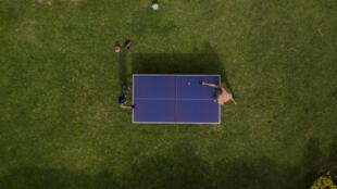 Dos jóvenes juegan al ping-pong en el jardín de su casa en Santiago el 22 de abril de 2020