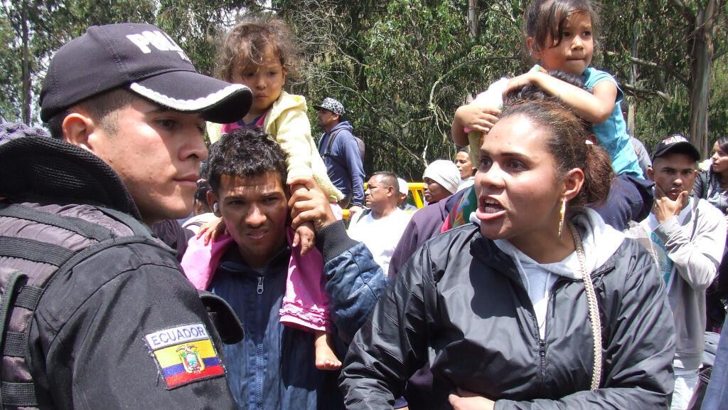 Una mujer venezolana increpa a un policía ecuatoriano en la frontera de este país con Colombia ante la negativa de las autoridades de dejar pasar a los migrantes que no posean la visa humanitaria.