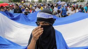 Manifestantes antigubernamentales sostienen una bandera nacional nicaragüense durante una manifestación contra el Gobierno del presidente nicaragüense, Daniel Ortega, en Managua, el 19 de abril de 2019.