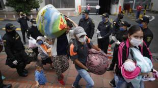 Un grupo de migrantes venezolanos lleva sus pertenencias este martes, durante su traslado en 10 buses hasta la frontera en Cúcuta, Colombia. Esperan llegar a Venezuela a pesar de las restricciones por la pandemia del nuevo coronavirus.