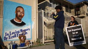 Activists look at a mural of Ezell Ford, a 25-year-old mentally ill black man, at the site where he was shot and killed by two LAPD officers in August, on December 29, 2014 in Los Angeles, California.