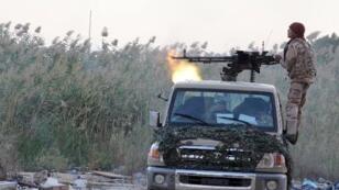 احد عناصر القوات الموالية للحكومة في ليبيا يطلق النار خلال هجوم على مناطق تسيطر عليها ميليشيات