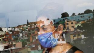 Mónica Samudio, de 46 años, cuyo esposo Jorge García, de 51 años, murió a causa de la enfermedad por coronavirus, se refleja en la ventana mientras mira hacia su nuevo departamento, en la Ciudad de México, México, 29 de abril de 2020.
