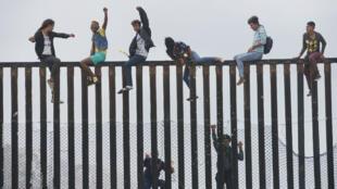 Des participants à la caravane des migrants escaladent le mur à la frontière entre le Mexique et les États-Unis, le 29 avril 2018.