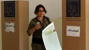 جندية عراقية كردية تدلي بصوتها في مركز اقتراع في عملية تصويت خاصة قبل الانتخابات التشريعية في 10 أيار/مايو 2018