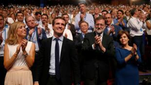 Pablo Casado reacciona después de haber sido elegido como el nuevo líder del Partido Popular conservador de España, como aplauden su esposa Isabel Torres Orts y el expresidente español Mariano Rajoy, en Madrid, España, el 21 de julio de 2018.
