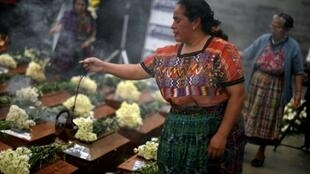 Indigenous women burn incense over urns with the remains of victims from Guatemala's 1960-1996 civil war after they arrived in San Juan Comalapa, Chimaltenango department, west of Guatemala City