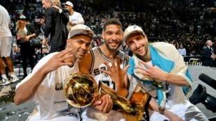 (g à d) Le trio Manu Ginobili, Tony Parker, et Tim Duncan, Trophée Larry O'Brien en main, après la défaite du Miami Heat à l'issue du match 5 des finales NBA, à San Antonio, le 15 juin 2014