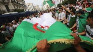 متظاهرون يرفعون العلم الجزائري خلال مظاهرات الجمعة 24 من الحراك. 2 أغسطس/آب 2019