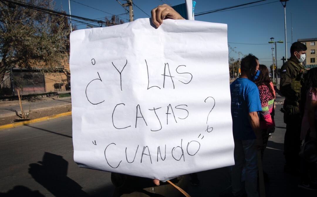 Un manifestante sostiene un cartel reclamando la entrega de cajas de ayuda durante una protesta contra el Gobierno del presidente chileno, Sebastián Piñera, en medio de la pandemia en Santiago el 25 de mayo de 2020.