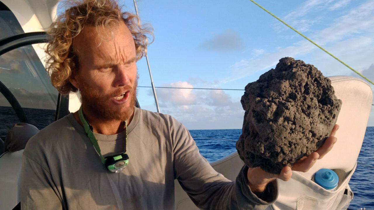Sail Surf ROAM muestra a Michael Hoult sosteniendo grandes piezas de piedra pómez después de recogerlo de una gran balsa de piedra pómez cerca de Tonga. 26 agosto 2019.
