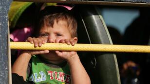 Un niño mira por la ventanilla de un autobús al llegar a Hama desde Deraa, Siria, el 21 de julio de 2018.