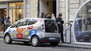 An Autolib user connects the vehicle to a charging station in Paris
