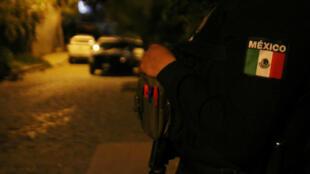 Un agente de policía custodia una escena del crimen en un barrio de Tlaquepaque, Jalisco, México , el 8 de julio de 2018.
