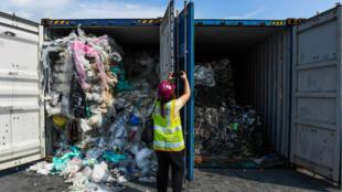 Un miembro de los medios de comunicación toma fotografías de contenedores llenos de desechos plásticos antes de enviarlos de vuelta al país de origen en Port Klang, al oeste de Kuala Lumpur el 28 de mayo de 2019.