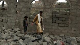 يمنيان بين أنقاض منزل استهدفته غارة جوية في صنعاء في 11 آب/أغسطس الماضي