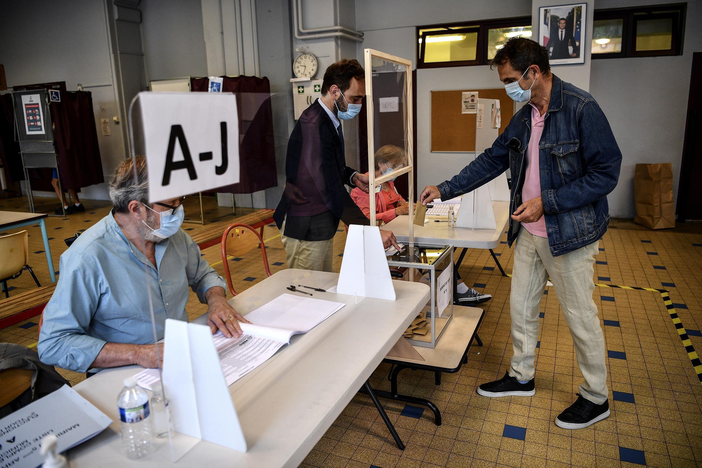 Un homme portant un masque met son bulletin dans l'urne dans un bureau de vote du 5earrondissement de Paris lors du second tour des élections municipales, le 28 juin 2020.