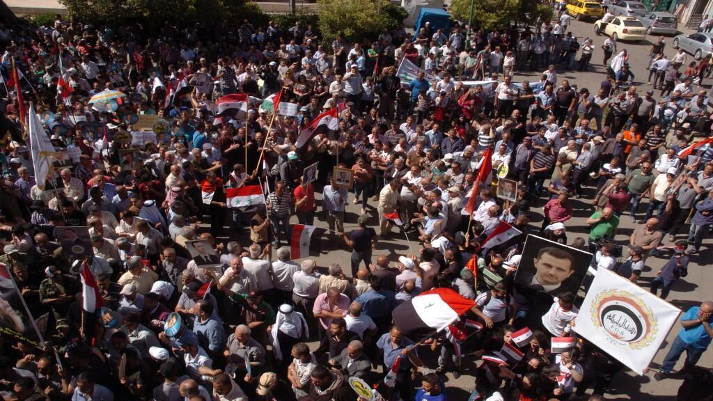 Los partidarios del presidente de Siria, Bashar al-Assad, llevan sus fotos y banderas durante una manifestación en la ciudad principalmente drusa de Sweida, Siria, en este folleto publicado por SANA el 10 de junio de 2020.