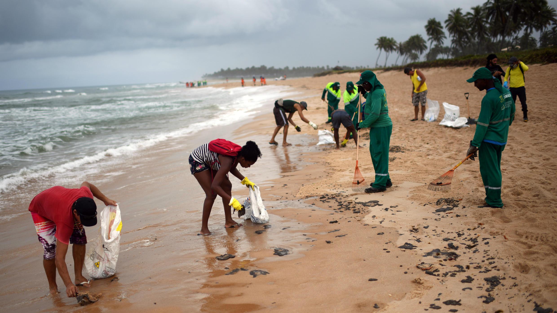 Des employés municipaux et des habitants nettoient les résidus d'hydrocarbures de la plage de Batta de Jacuipe, à Camacari près de Salvador de Bahia, le 22 octobre 2019.